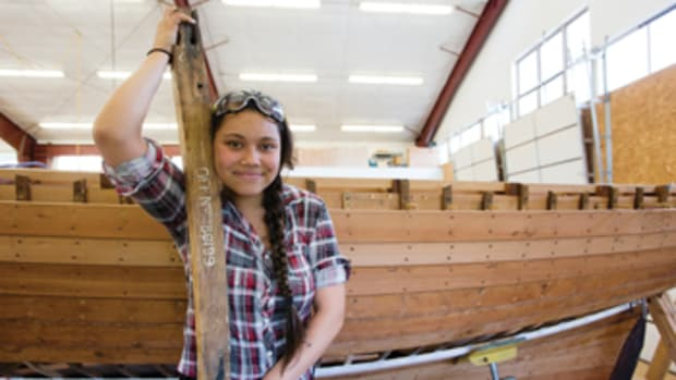 Tatyana Faledo-Nolan, a student, with the boat's original deck beam.
