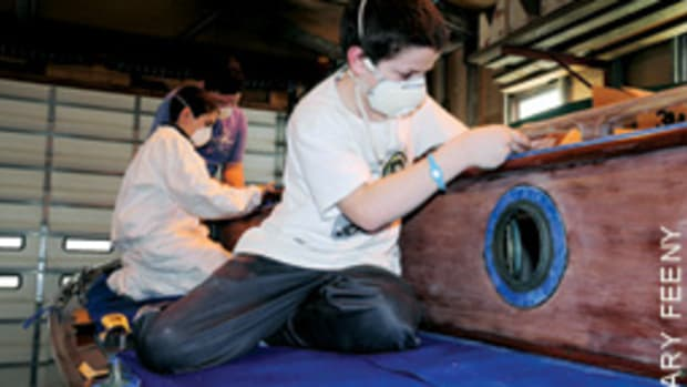 Students in the Herreshoff Institute's After-School Boat Shop Program prep a boat for varnish.