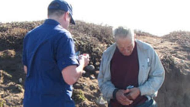A Coast Guard crewman interviews the skipper after his rescue.
