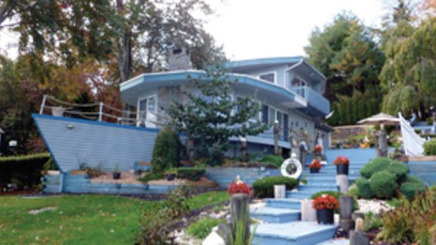 The tug-shaped house replaced a fire-destroyed cottage; the kitchen has glass-front cabinets; a swimming pool and spa overlook Hitchcock Lake.
