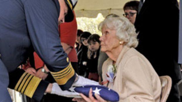 Miriam Webber, wife of Bernard Webber, accepts a ceremonial flag from Coast Guard Commandant Adm. Thad Allen during a graveside ceremony in Wellfleet, Mass., May 9.