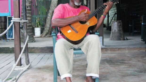 """Foxy and his guitar are a familiar and beloved sight on Jost Van Dyke. When the man himself is not in residence, an """"Epoxy Foxy"""" greets the bar's visitors."""