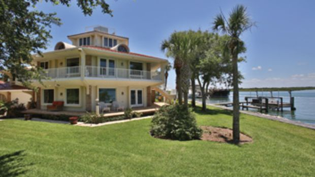 This home in Ponce Inlet, Florida, is angled to take advantage of views; the kitchen's custom granite-topped cherry cabinets extend almost to the ceiling; cut stones pave the patio around the swimming pool and spa.
