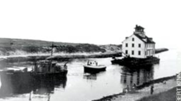 A towboat enters Menemsha Creek in summer 1952, pulling a barge carrying the new Menemsha station from Cuttyhunk, Mass.