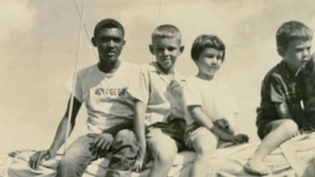 Deckhand Joe Cranston, Lou Boudreau, and his siblings Janene and Peter, on the boom of the schooner Ramona.