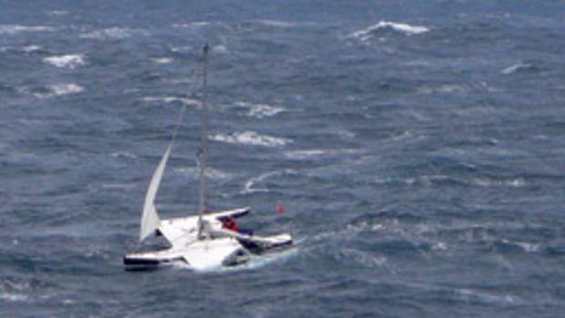 Barham awaits rescue aboard his battered Val 31 trimaran.