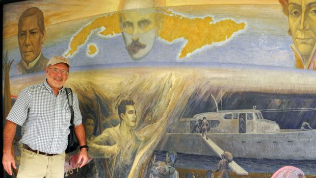 The author poses in front of a mural in Tuxpan on Mexico's Gulf Coast, which shows Granma being provisioned for the invasion of Cuba. Tuxpan was the departure point for Raul Castro's historic 1956 expedition. Among the 82 men on board was Che Guevara and Castro himself.