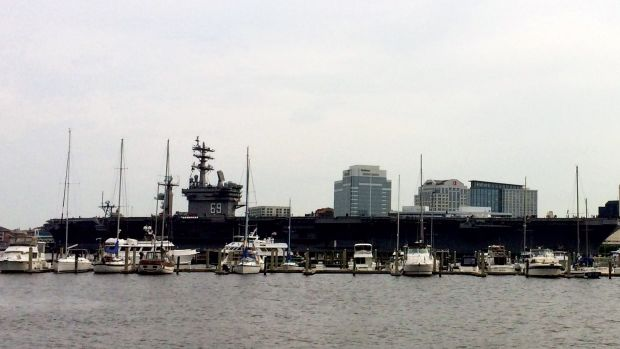 large ship passing behind smaller boats