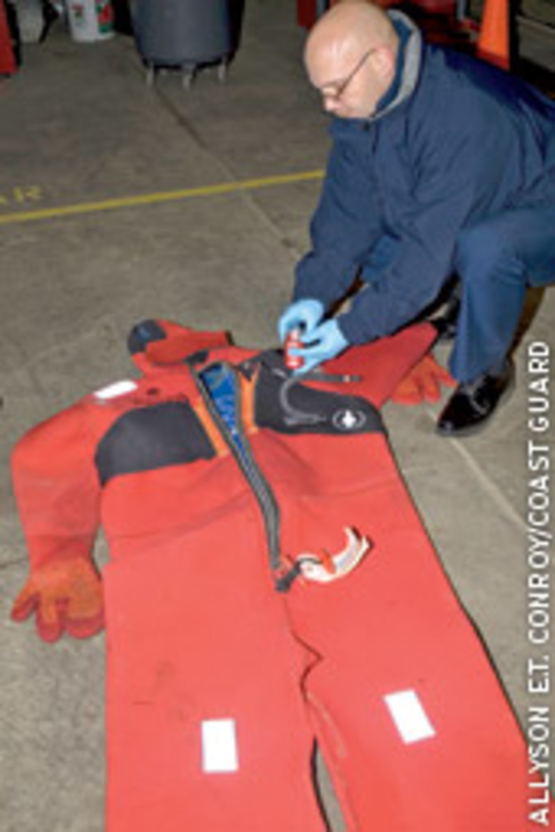 Cmdr. Malcolm McLellan, Marine Board of Investigation chairman, inspects the strobe on a survival suit.