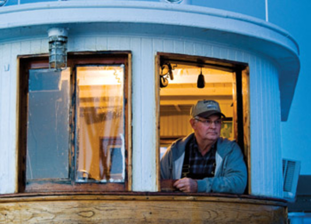 Capt. Jerry Pruitt peers out of the pilothouse aboard Delvin K, one of the last working oyster buyboats on Chesapeake Bay.
