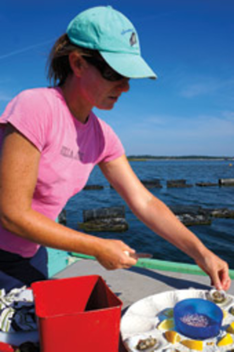 Abigail Carroll shucking Nonesuch oysters on her workboat.