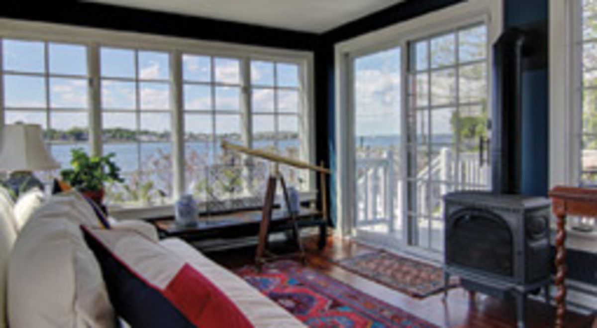 Three walls of windows offer water views from the sunroom.