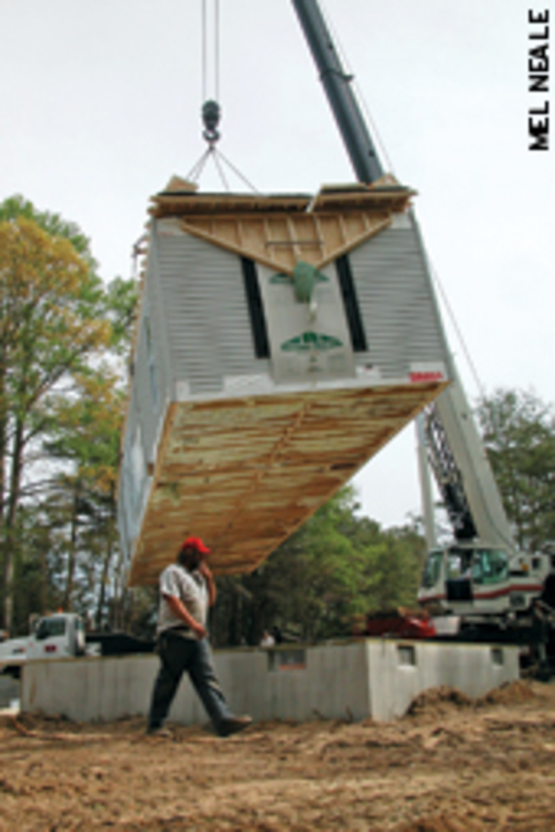 A crane gets positioned to set a section of the house on its foundation.