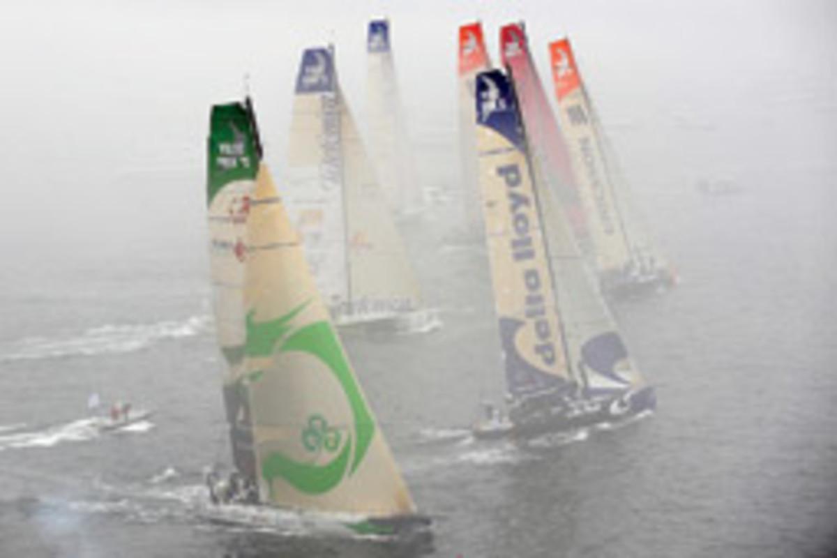 The Volvo Ocean Race fleet, covered in fog, sails in the Boston in-port race at Fan Pier.