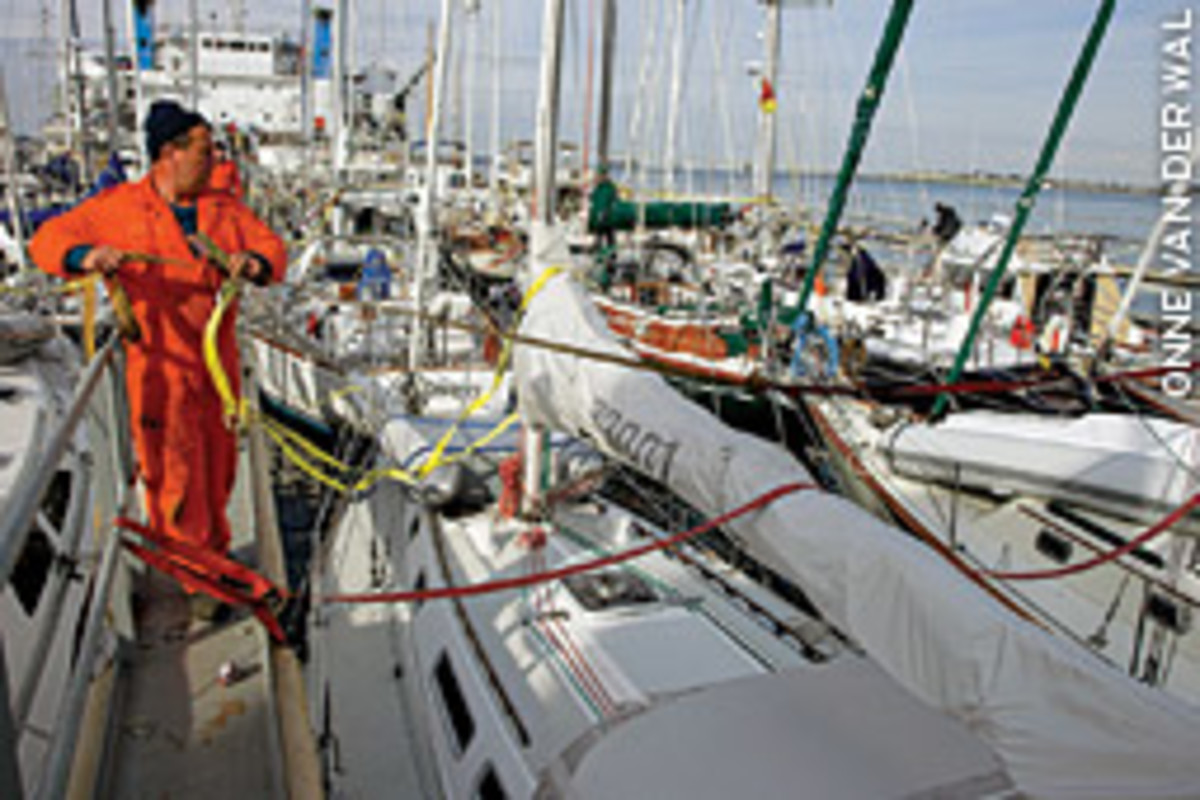 Crewmembers secure straps so the yachts won't shift when the carrier deballasts and the sumbersible refloats.