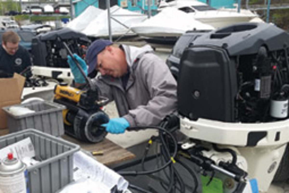 Adey installs new hydraulic steering line fittings while preparing a boat for this summer's ethanol-alternative fuel testing.