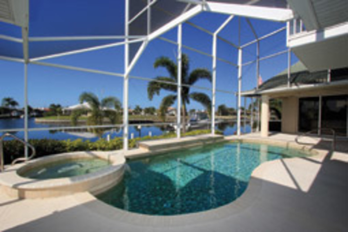 The two-story screened enclosure covers the pool and spa.