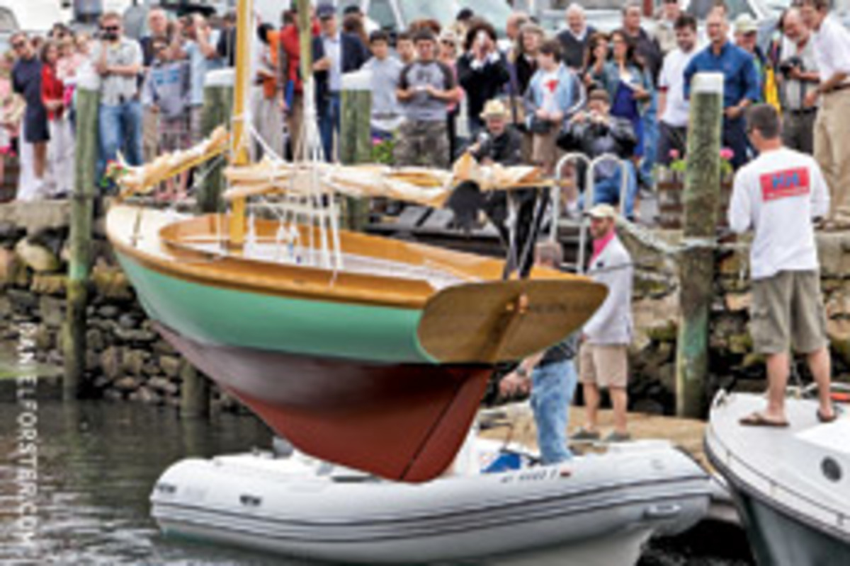 A Herreshoff 12 1/2-footer is lowered into the water at the International Yacht Restoration School's graduation ceremony. Fourteen students graduated from the Boatbuilding & Restoration program this year; 12 from the Marine Systems program.