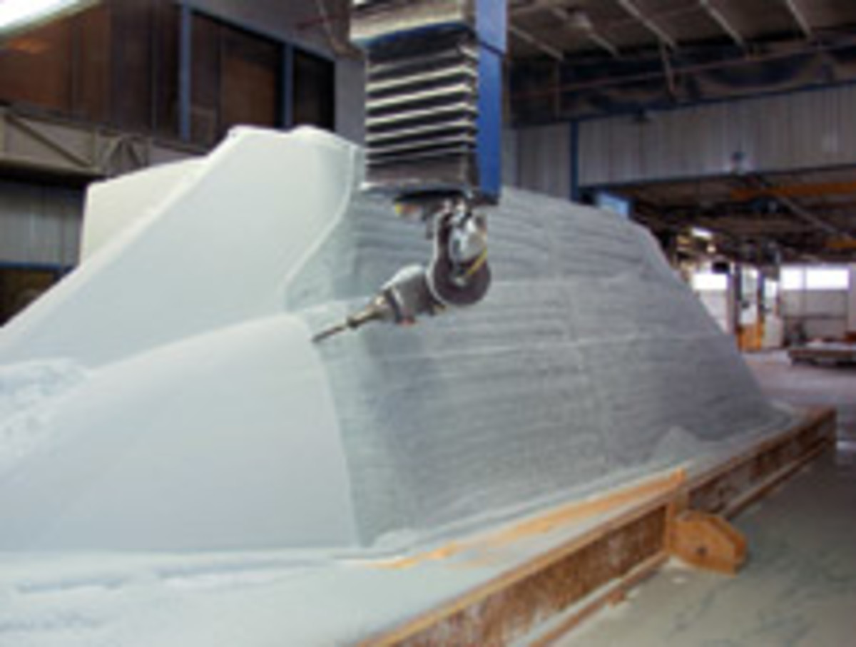 Viking's computer-operated five-axis milling machine shapes a deck assembly plug from which a fiberglass mold will be made for the new 52 ST.