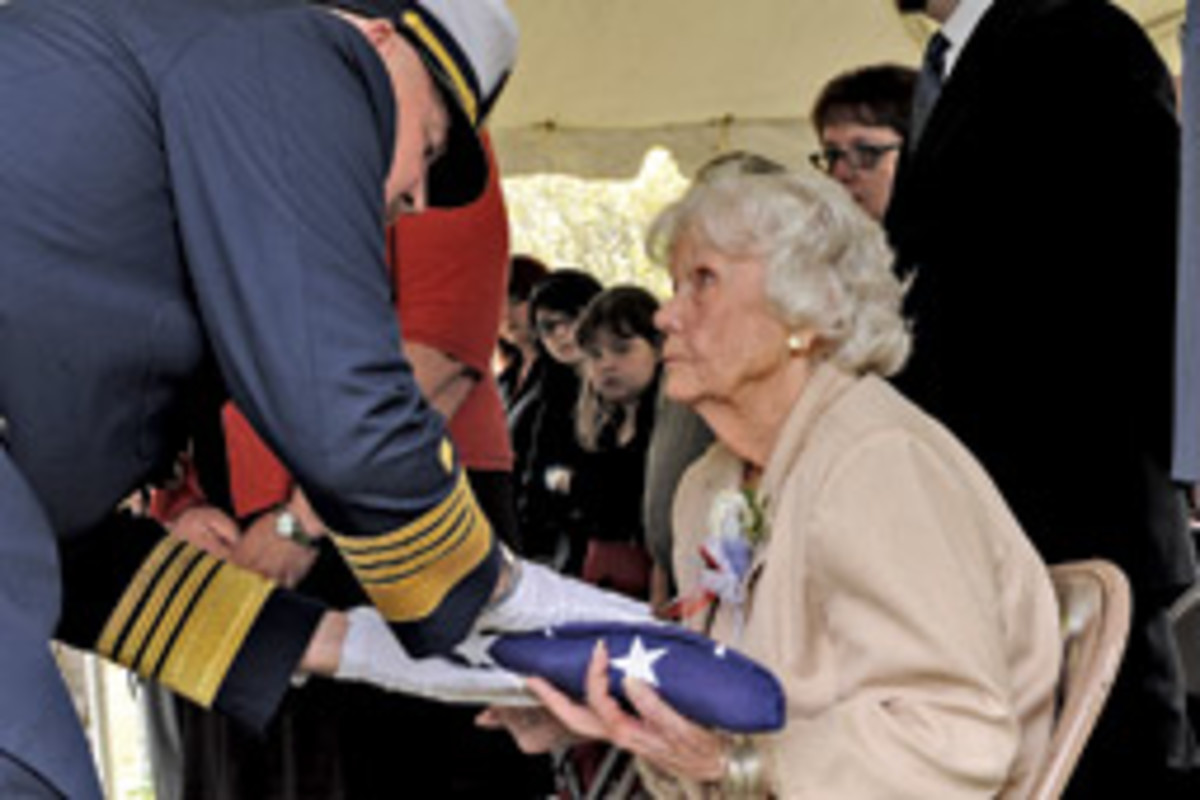 Miriam Webber, wife of Bernard Webber, accepts a ceremonial flag from Coast Guard Commandant Adm. Thad Allen during a graveside ceremony in Wellfleet, Mass., May 9.