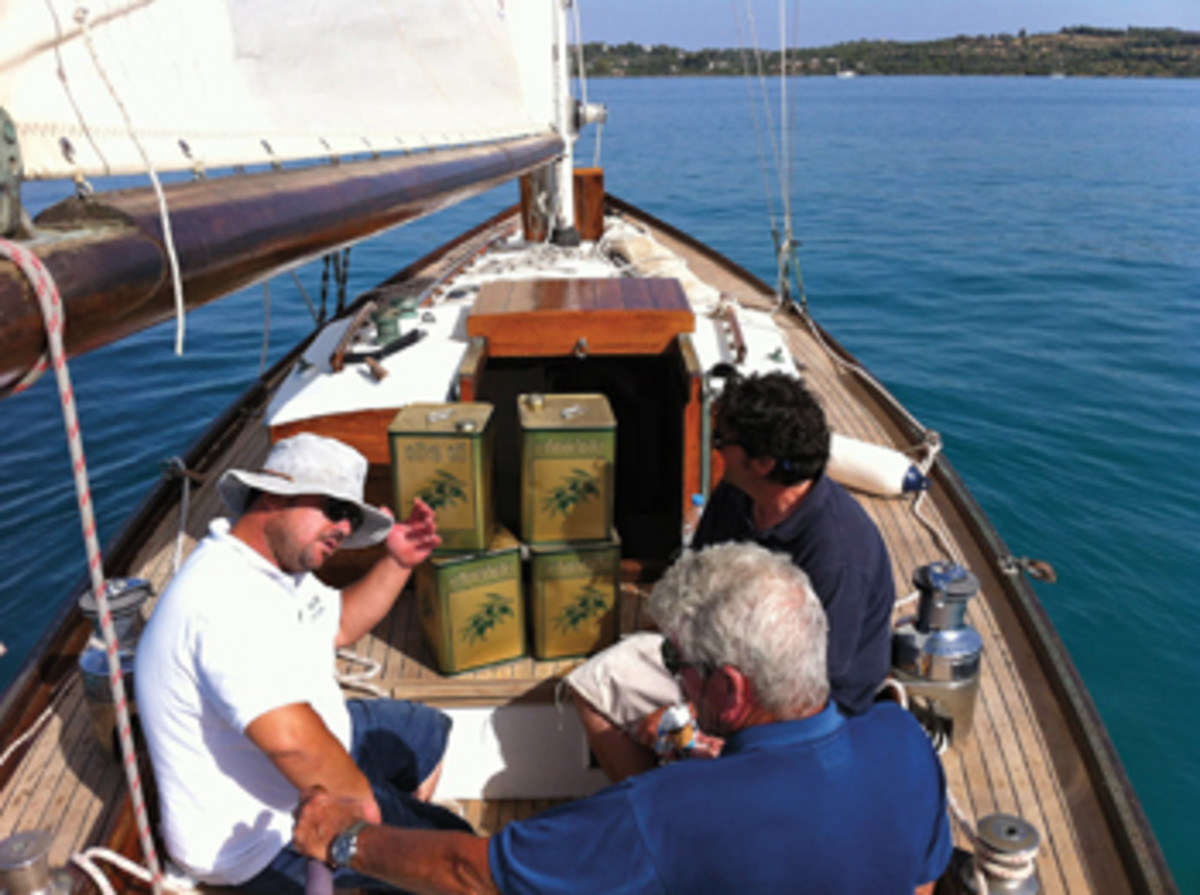 A tender carries olive oil delivered by the sailing ship Tincano from Pelopennese to Spetses, Greece.