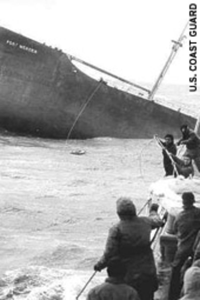 Crewmen of the U.S. Coast Guard Yakutat draw in a rubber life raft with the last two survivors from the bow section of the broken tanker Fort Mercer.