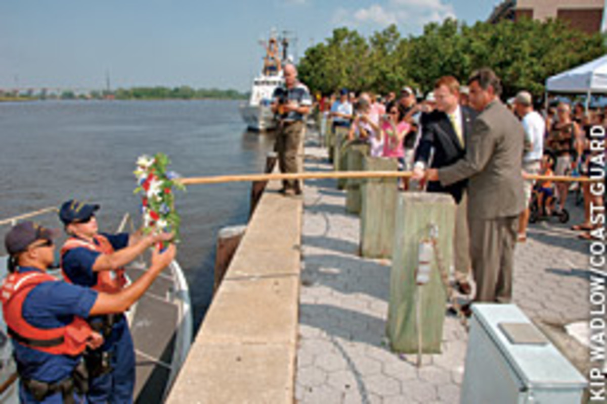 Coast Guardsmen Houston Edwards and Joseph Harris, from Coast Guard Station Oak Island, N.C., accept a wreath from congressman Mike McIntire and Wilmington Mayor Bill Saffo.