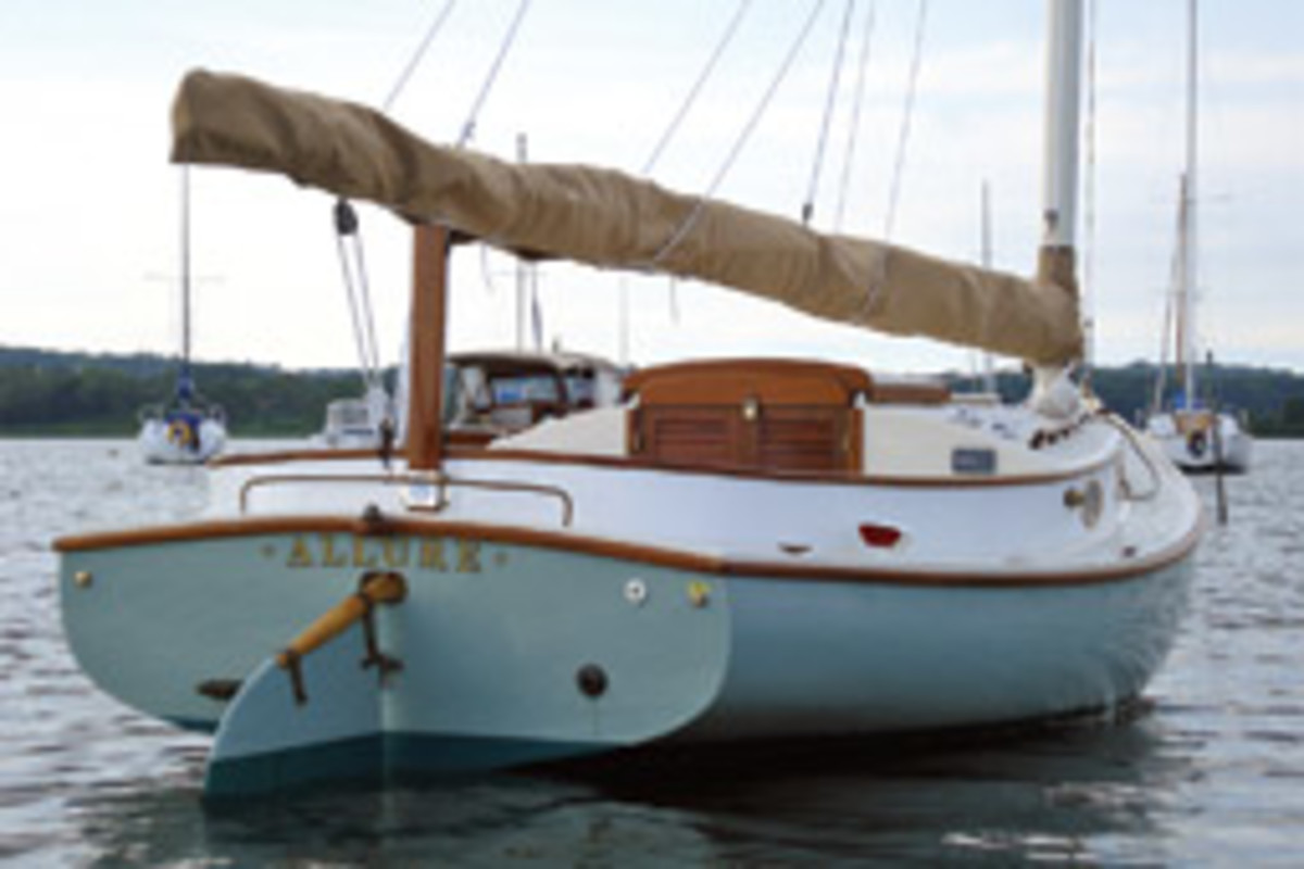 Allure, with her light green hull, stands out among catboats.