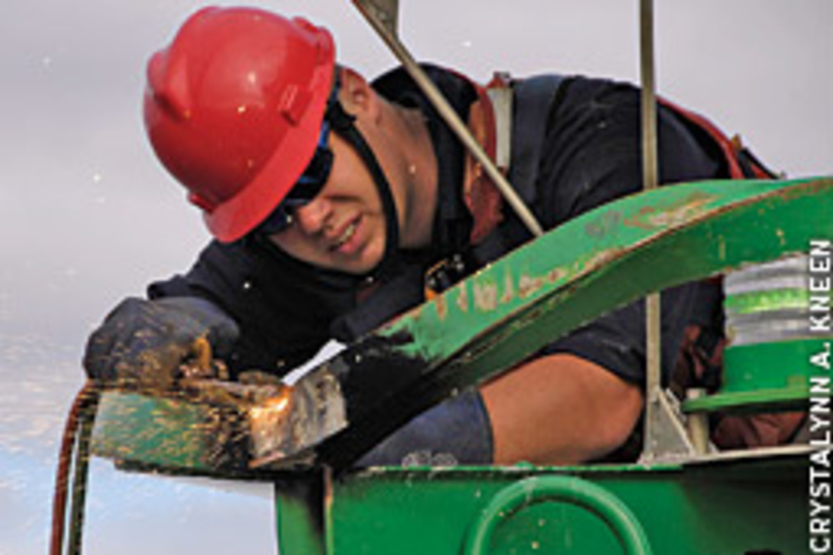 Petty Officer 2nd Class David Mann repairs a buoy damaged by a tugboat in the Delaware River.