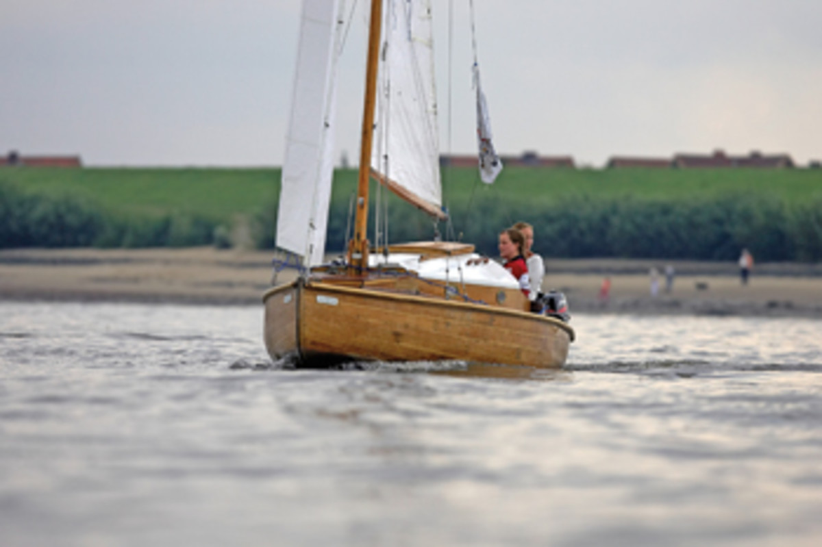 Ronja, 10 years ago, cuts a nice wake on the Elbe River, with Jenny at the helm and Mareike tending the jib.