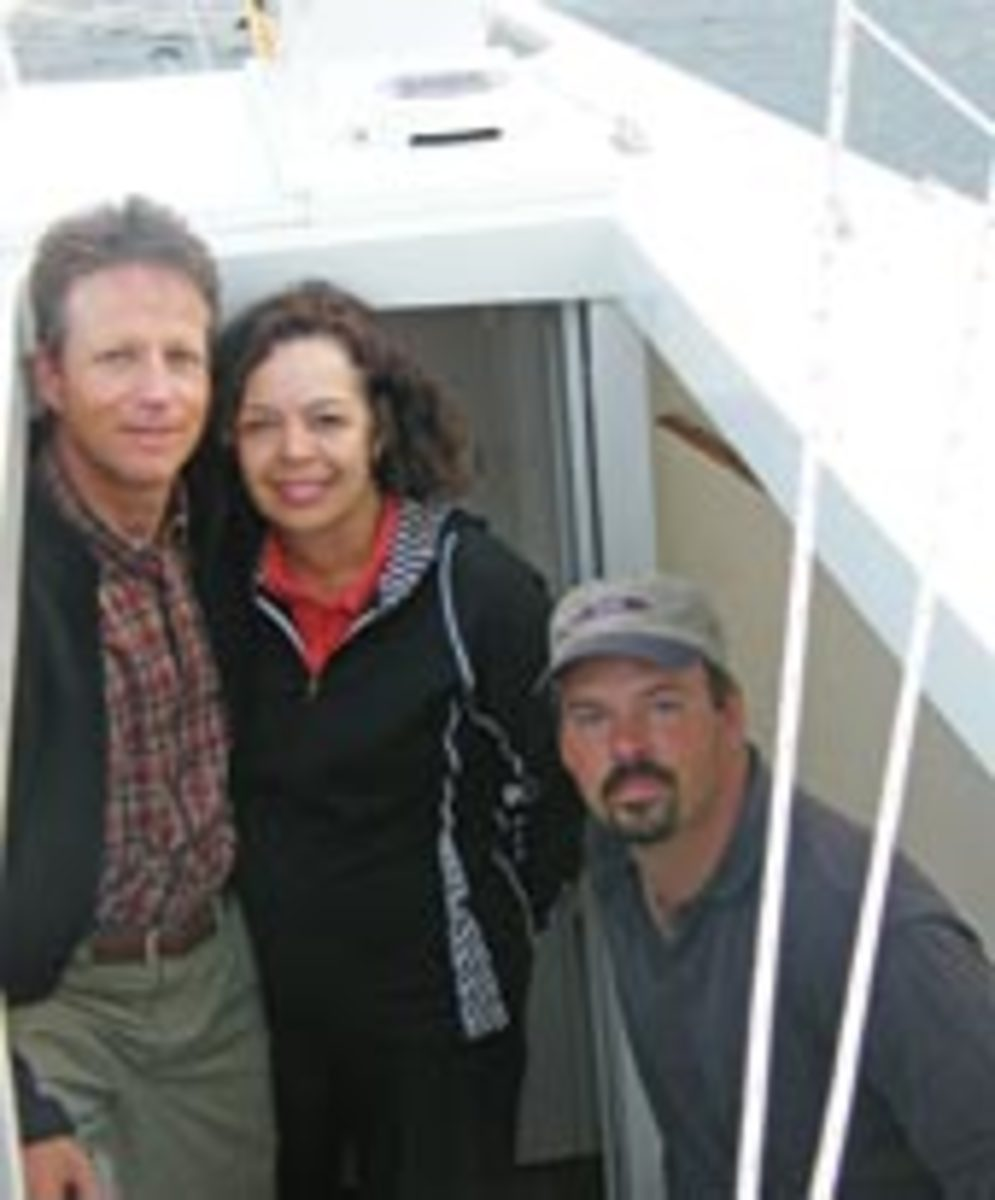 Ted Derivan, left, with the owners of a 27-foot Phil Bolger-designed birdwatcher-style sharpie schooner he built for them.