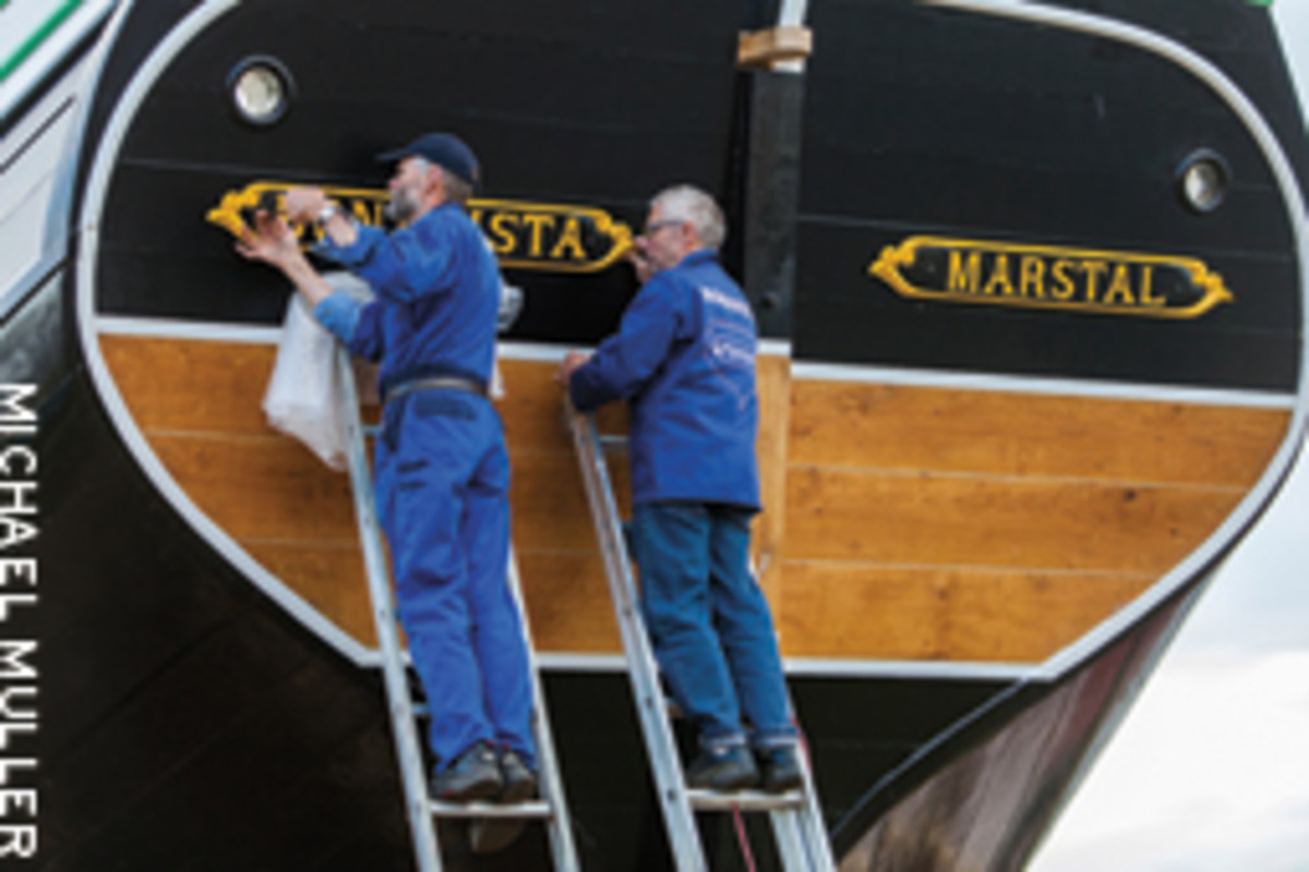Master boatbuilder Ebbe Andersen (right) helps with the finishing touches.