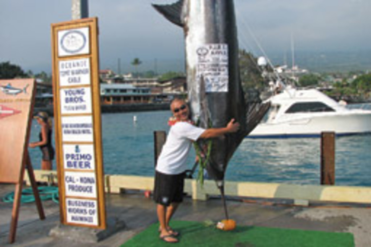 Ted Morikawa, an angler aboard Out of the Blue, hugs his 779-pound blue marlin - the largest fish landed at this year's Hawaiian International Billfish Tournament.