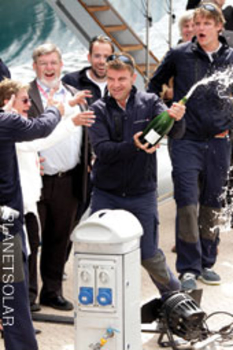 Erwann LeRouzic, PlanetSolar's second captain, breaks out the bubbly as the crew celebrates.