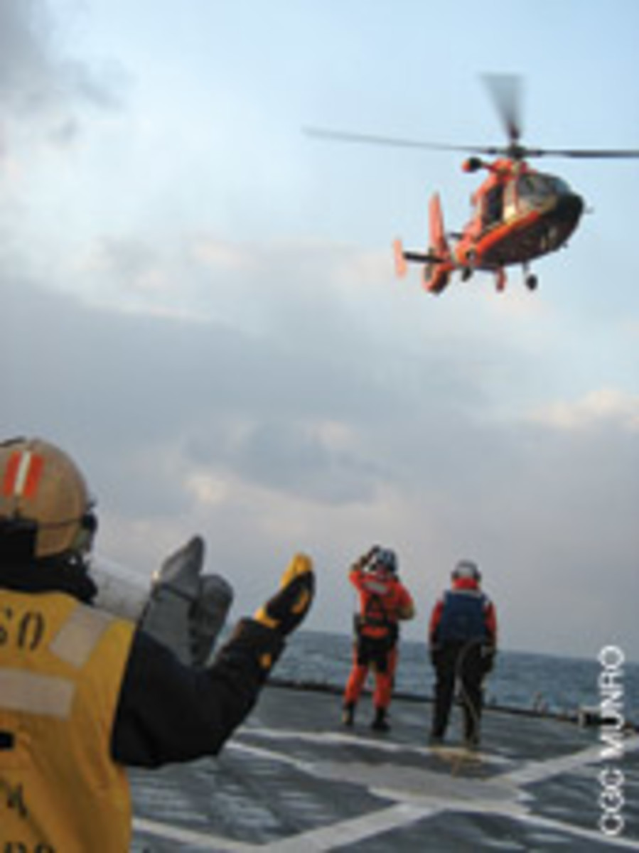 Crew aboard the Coast Guard cutter Munro wait for survivors from the Alaska Ranger to arrive by helicopter.