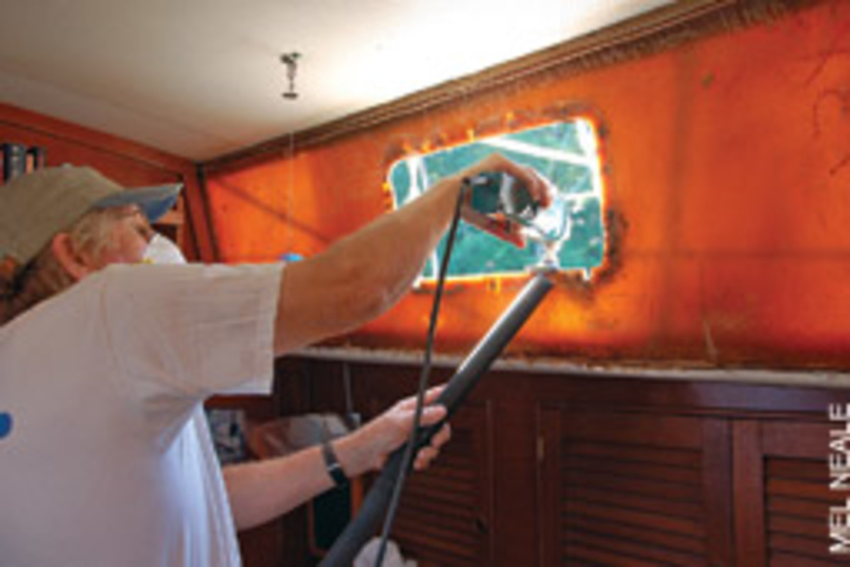 It's dirty work, but someone's got to do it. When the decision was made - by Tom's wife - to replace Chez Nous' portholes, he first had to wage war against 3M 5200 adhesive. Craftsman Dave Peresluha (above) was called in for the cutting and fitting.