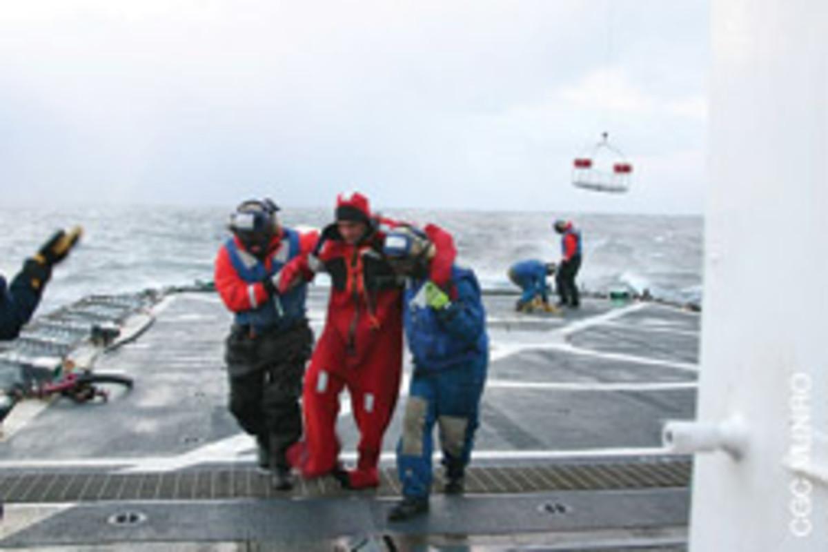 Seamen Gregory Crane and Nathan Cramer assist a crewmember from the Alaska Ranger.