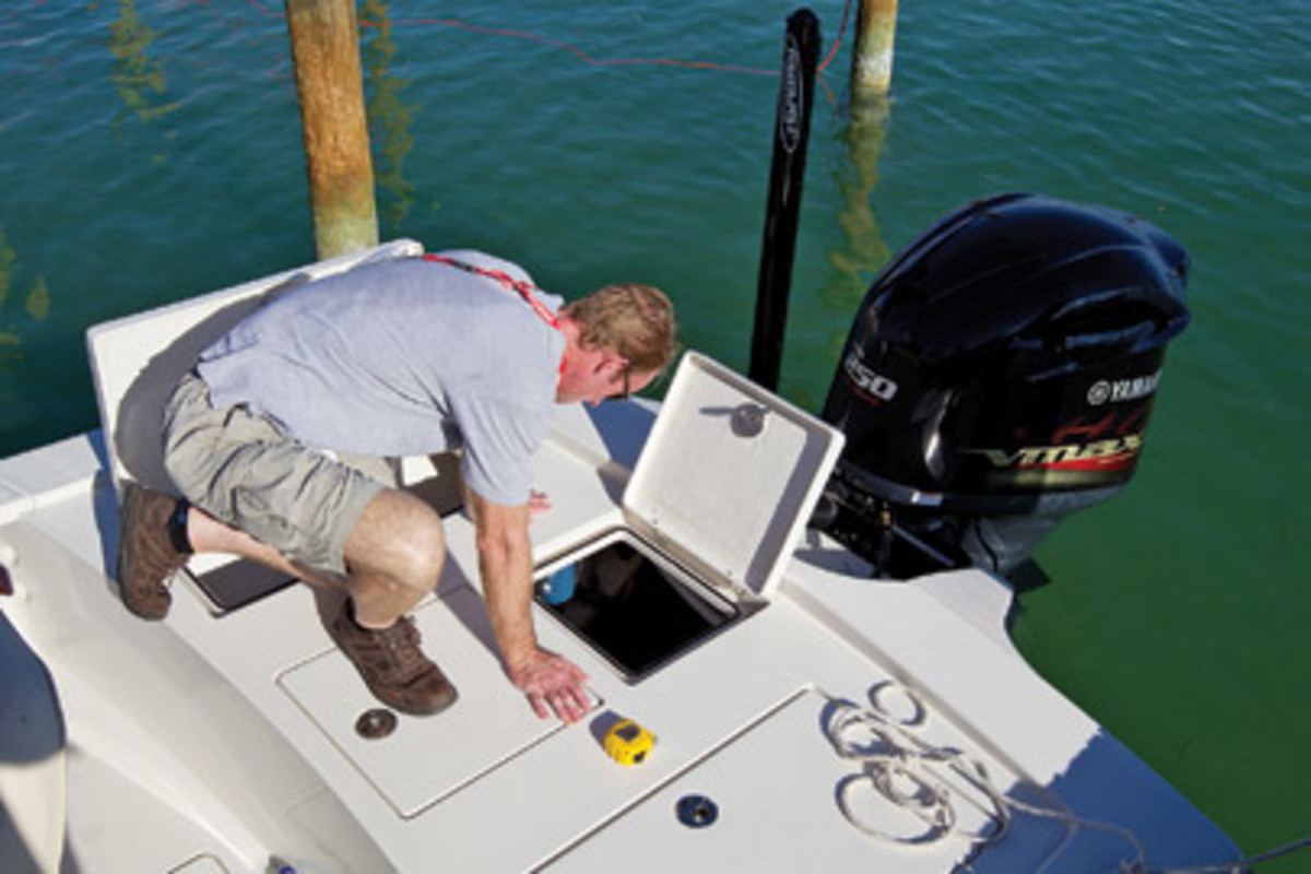 The writer looks into the aft hatch of a 23-foot bay boat to evaluate access to the fuel lines and the filter.