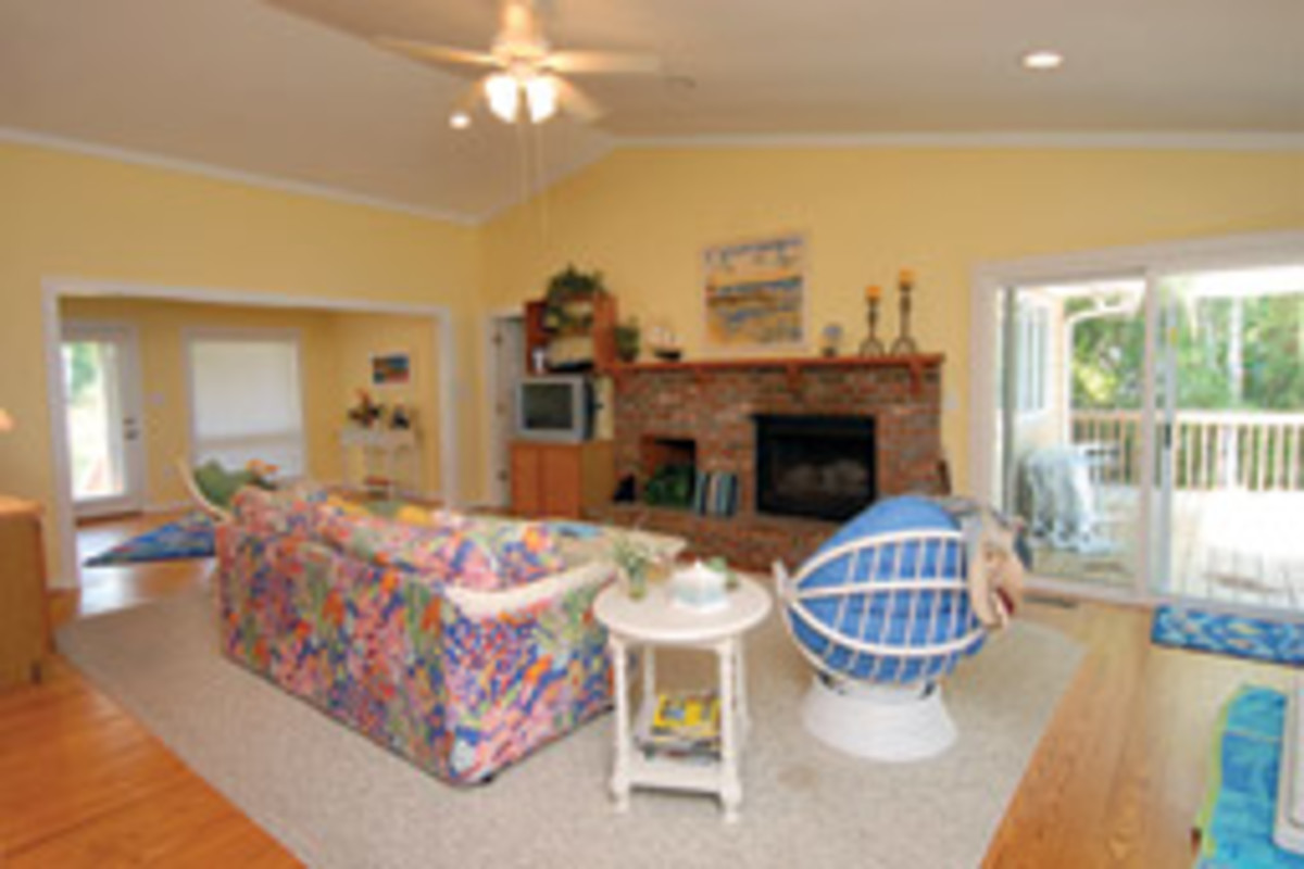 The great room features a brick fireplace, and the sliders at right open to the deck.