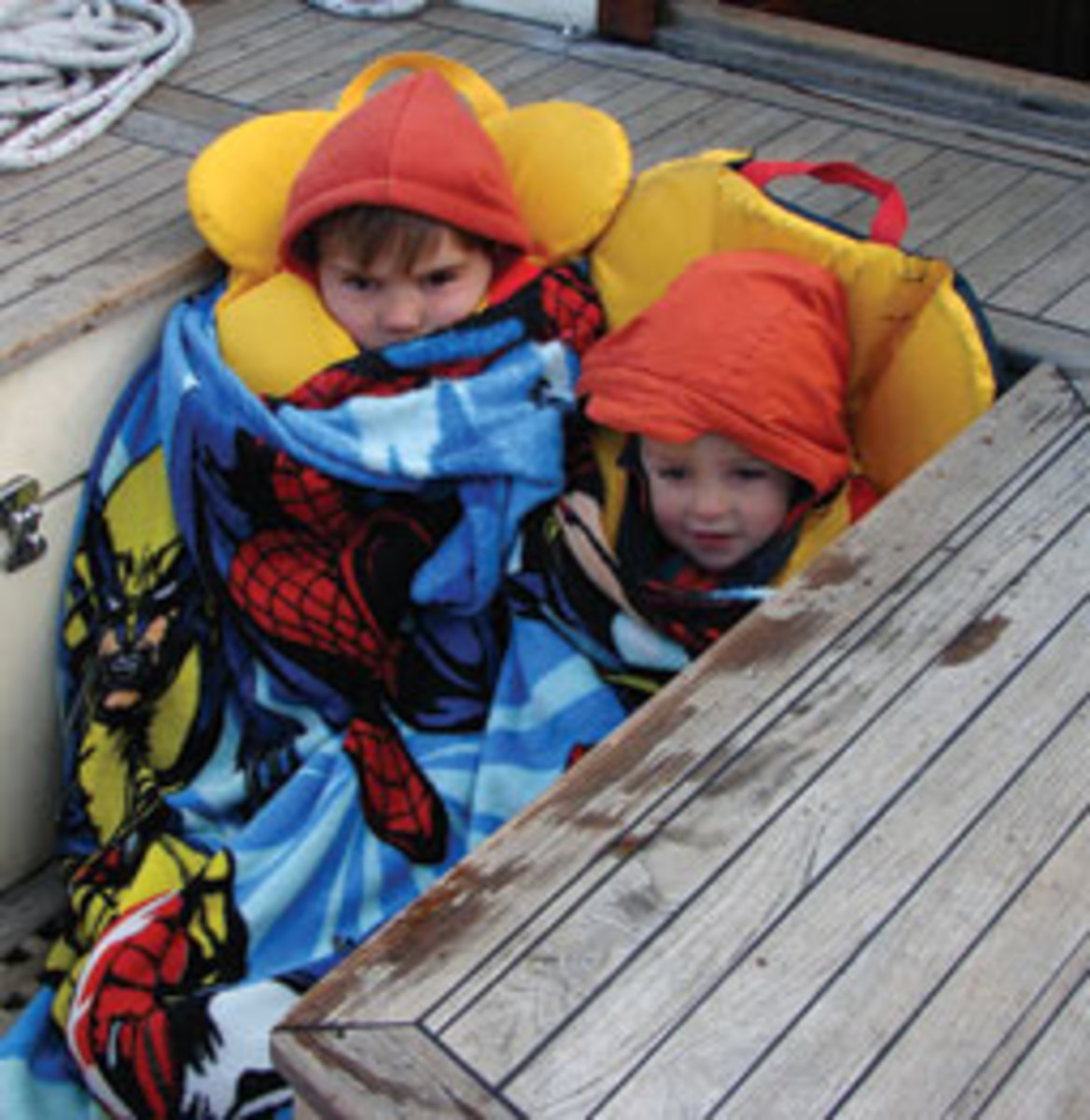Emil and his younger brother, Peter, stay warm and safe on a chilly day for sailing.
