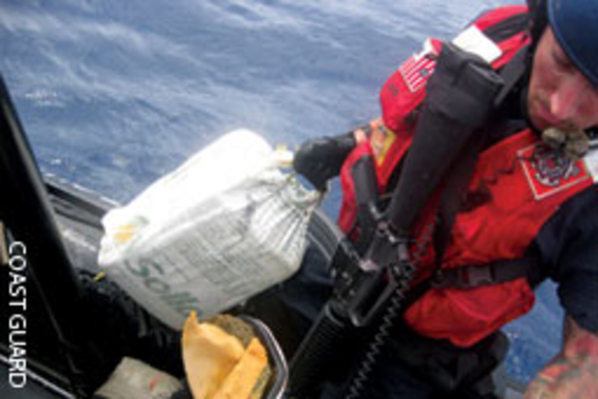 A Coast Guardsman carries a bale of cocaine interdicted Sept. 17 from a self-propelled, semi-submersible vessel in the Caribbean Sea.