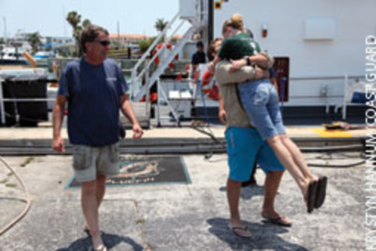 Dave Mandigo watches as his niece, Morgan Mandigo, embraces her boyfriend, Jhade Woodhall, following their rescue.