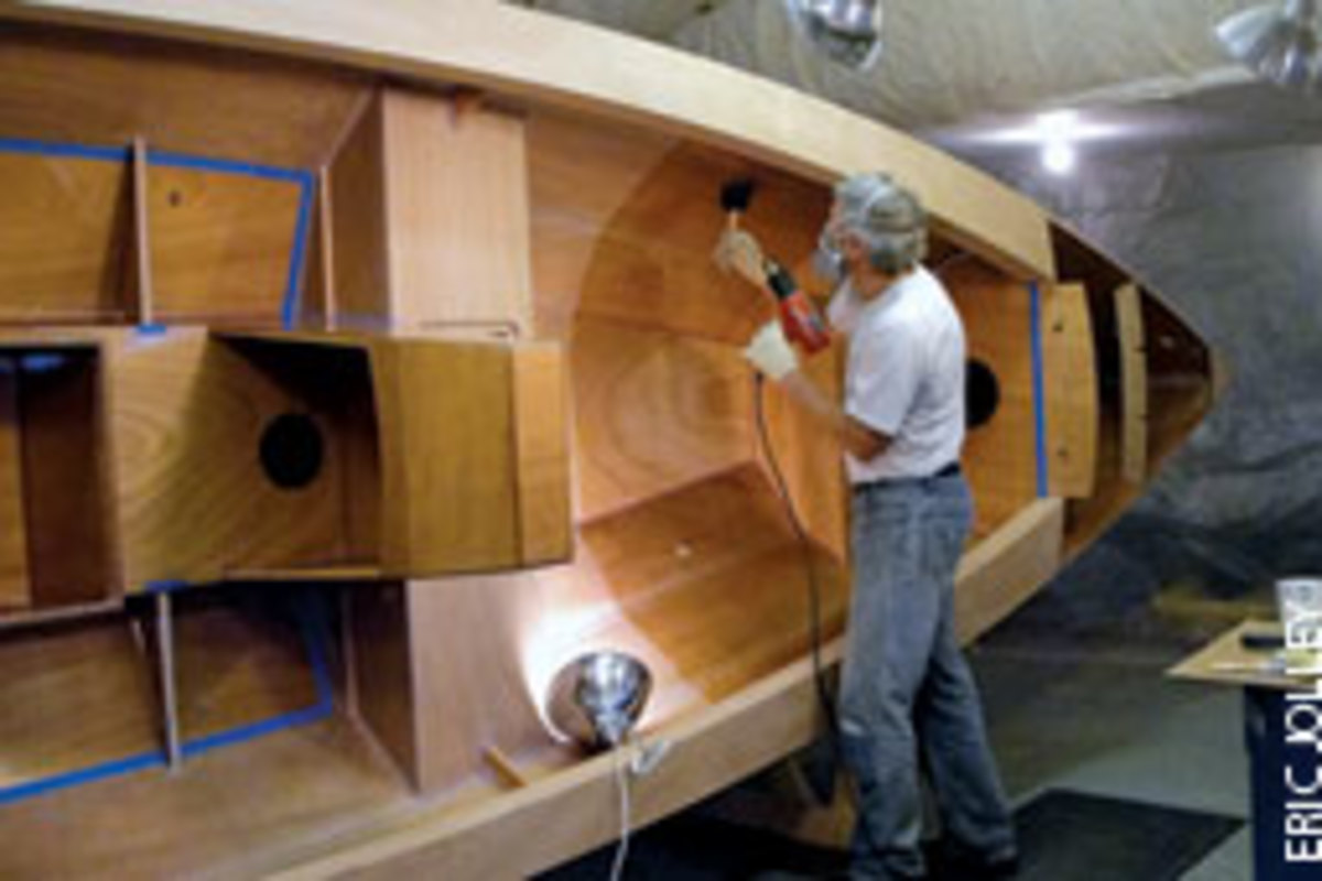 Port Townsend Watercraft owner Russell Brown applies epoxy to the interior of the skiff.