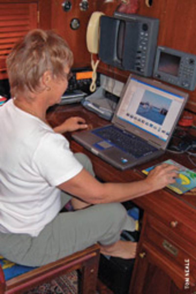 The nav station aboard Chez Nous makes a cozy office for Tom's wife, Mel.