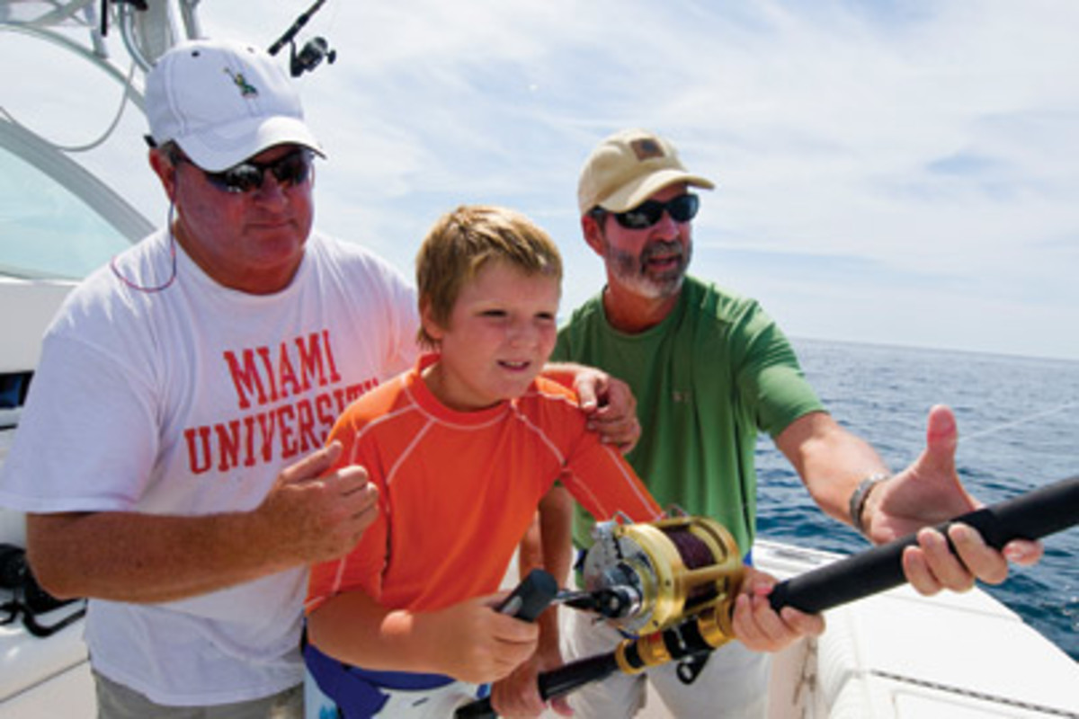 Ted O'Connor (left) and Soundings editor Bill Sisson steady Bill's son, Michael, 11, as he fights his first shark.
