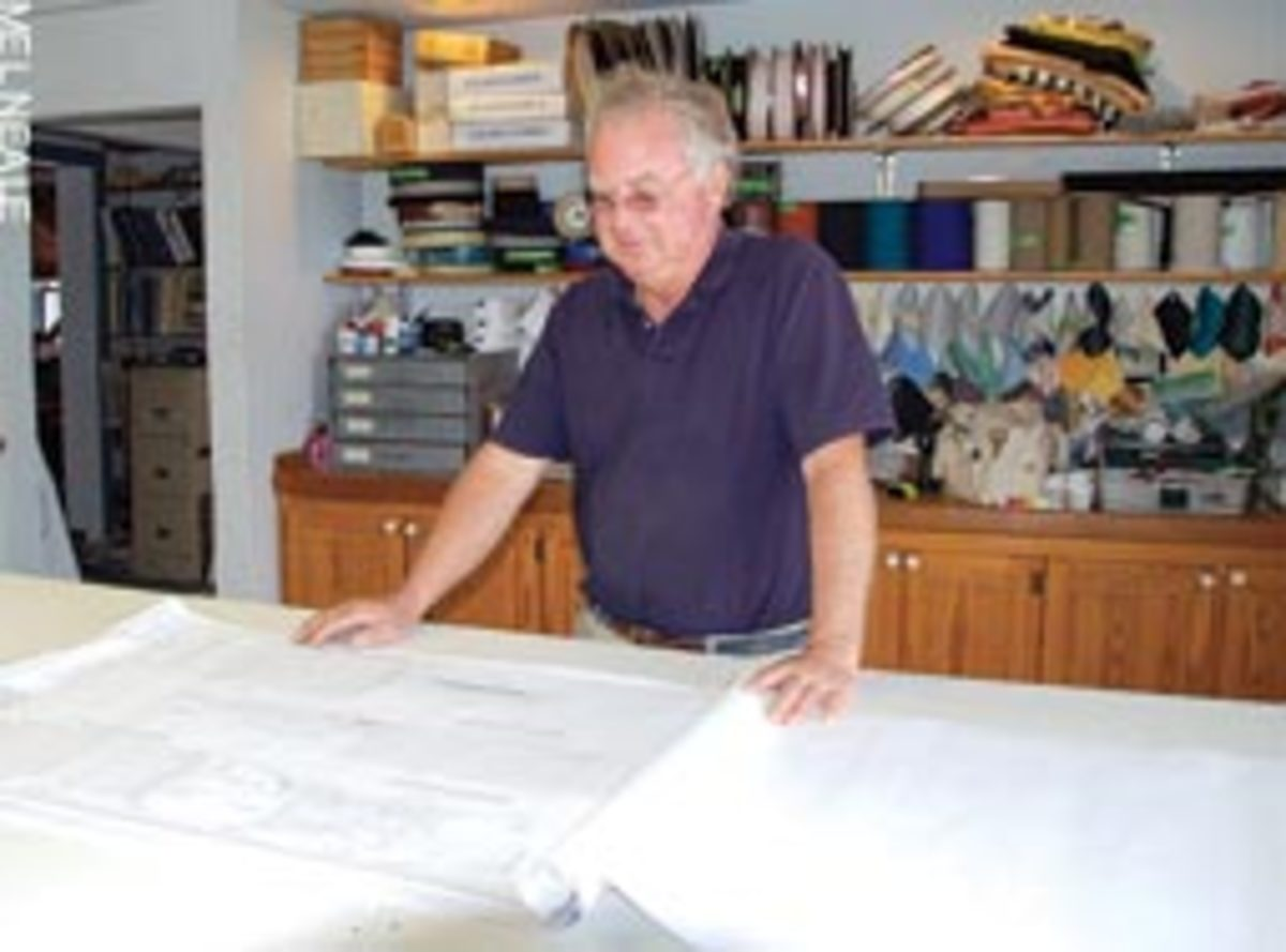 Inside the Interior and Canvass workshop, which was not damaged, Randy Cockrell looks over the architect's plans for the new work spaces.