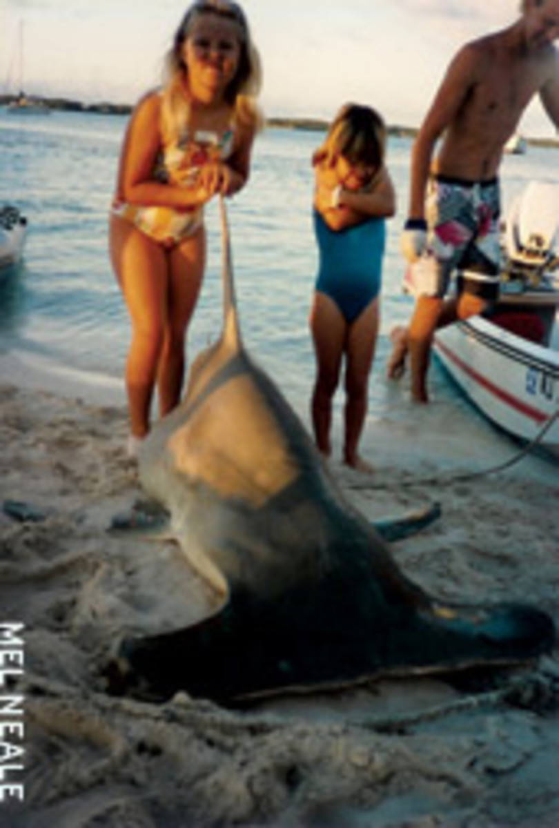 Tom's daughters, Melanie and Carolyn, with a hammerhead caught in a popular harbor in the Exumas many years ago.