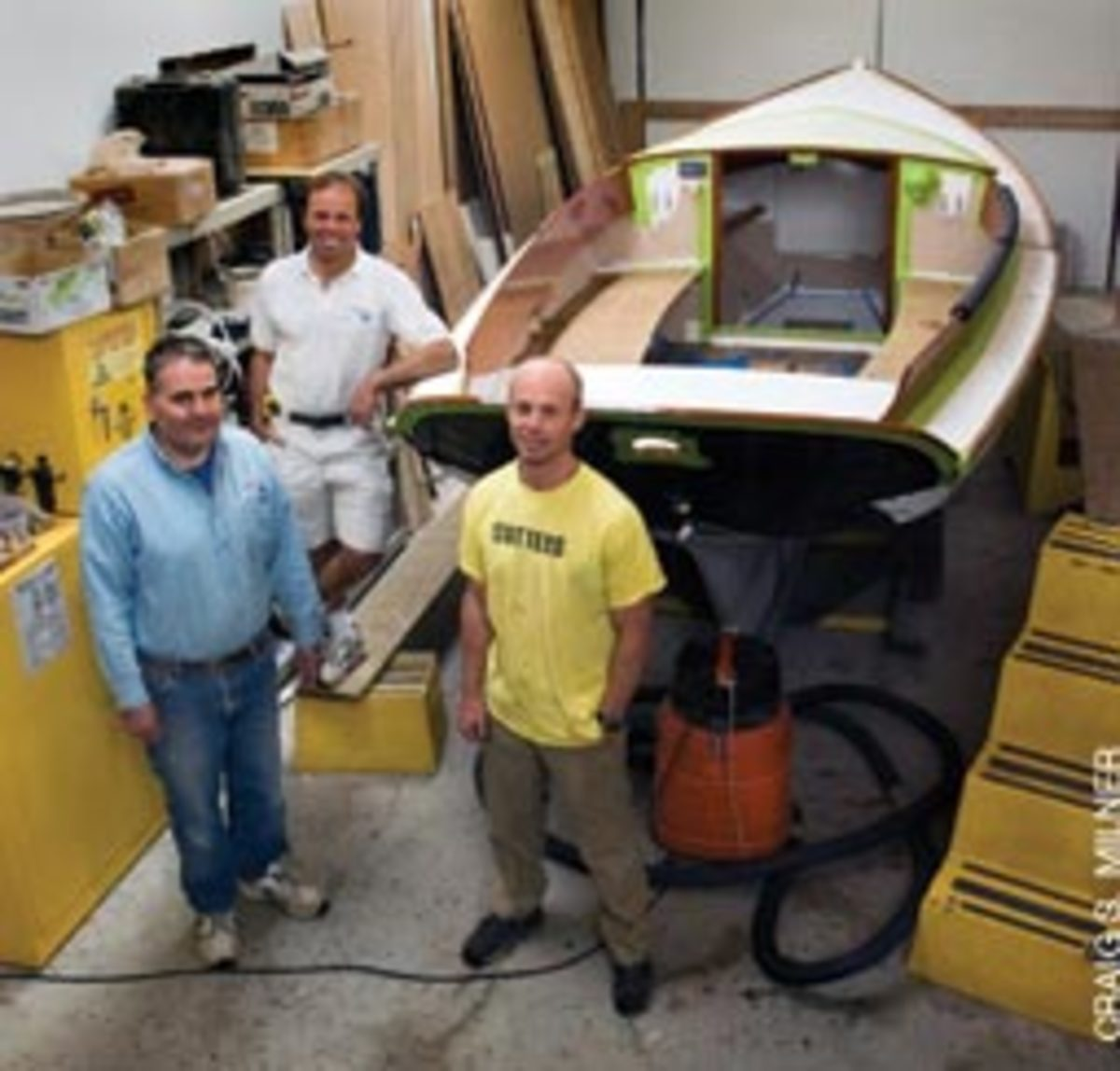 Jean Beaulieu (back), Tom Gilpatrick (left) and Stephen Linscott stand with one of the Pisces 21s in progress. These days Classic Boat Shop employs about 10 people, depending on the time of year.