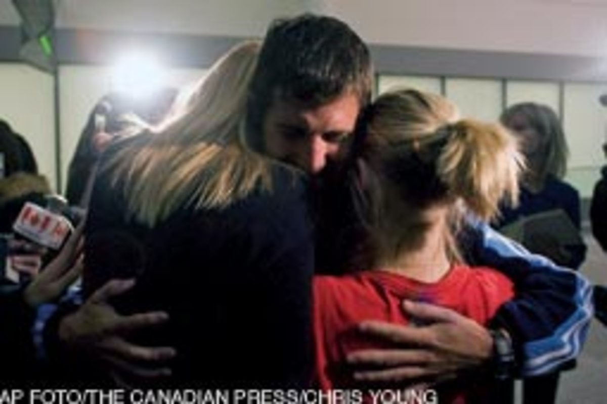 A teacher aboard Concordia receives an emotional welcome home at Toronto's Pearson International Airport.