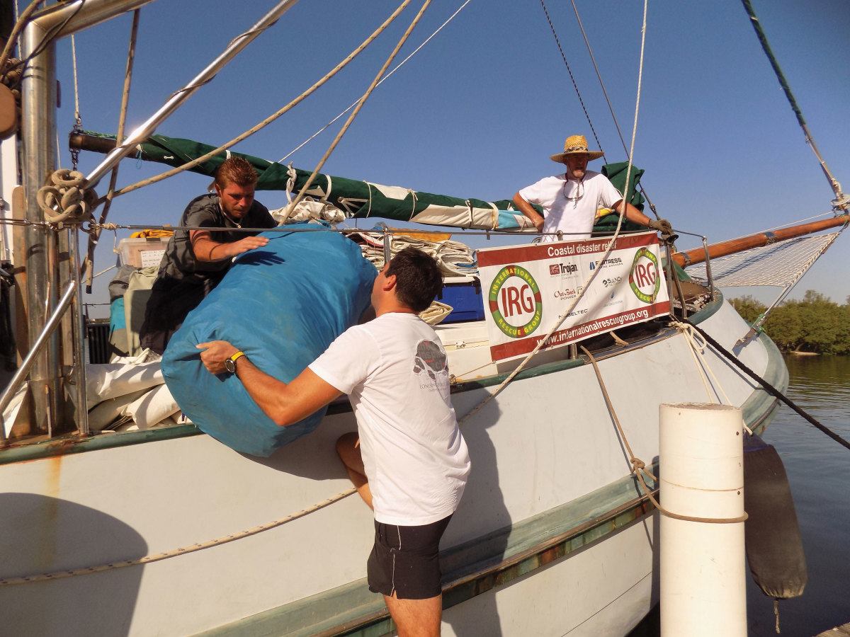 Volunteers load desalinators  and used sails for fishermen aboard Thunderbird V.